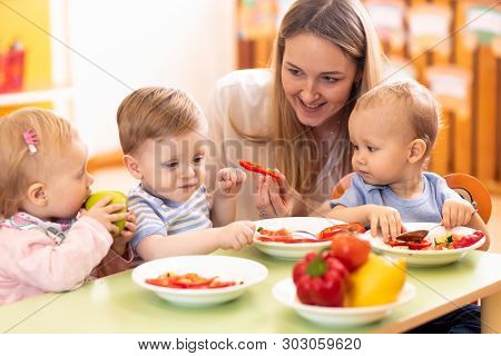 Kids Have A Lunch In Day Care Centre. Children Eating Healthy Food In Kindergarten. Nursery Teacher