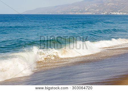 Splashing Wave, Followed By A Swelling Wave On Ocean Expanse, Foaming Backwash On A Sandy Beach