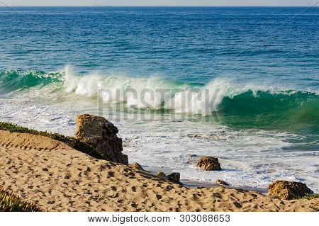 Breaking Transparent Turquoise Wave With Backwash And Backspray On A Sandy Beach