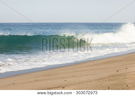 Splashing Wave Breaking From Swelling Wave In Froth Of Backwash On Sandy Beach