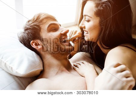 Young Sexy Couple Have Intimacy On Bed. Lying Together And Smile. Woman On Man. Beautiful Sexy Attra
