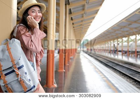 Woman Traveler With Backpack Talk On Mobile Smart Phone At Train Station. Trip Journey Travel Concep