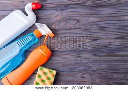 House Cleaning Supplies On Wooden Background. Set Of Plastic Bottles With Cleaning Liquid And Kitche
