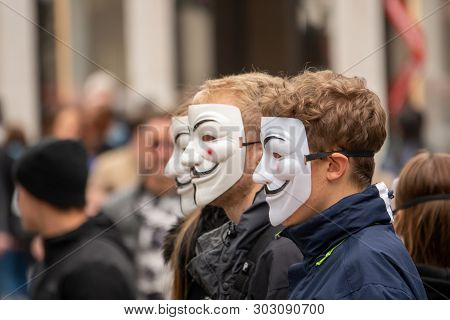 A Group Of Young People Dressed All In Black Goes Out On The Street To Demonstrate With Anonymous Ma