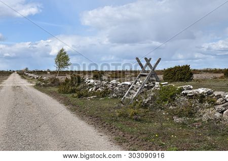 Wooden Stile By A Dirt Road In A Great Plain Grassland, A World Heritage Site At The Swedish Island
