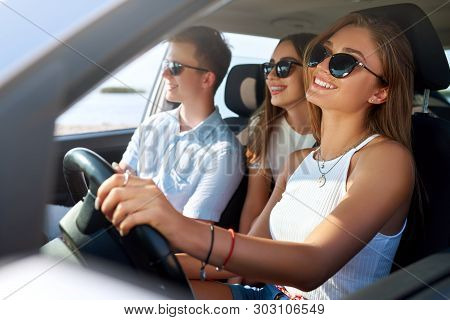 Group Of Friends Rented A Car On Summer Road Trip And Arrived To The Sea Beach. Girl Having Fun With