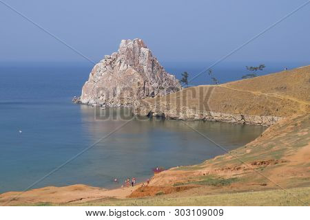 Lake Baikal. Olkhon Island. Village Khuzhir. In The Foreground Is A Small Beach. Several People Are