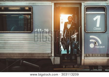 A Fancy Bald Bearded African Businessman In Glasses And With Travel Bags In His Hands Is Leaving The