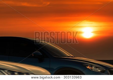 Side View Of Blue Suv Car With Sport And Modern Design Parked On Concrete Road At Sunset. Hybrid And