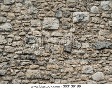 Old Beige Stone Wall Background Texture Close Up. Texture Of A Stone Wall. Old Castle Stone Wall Tex