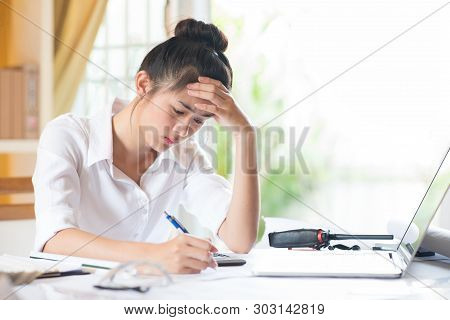 Stressed Businesswoman With Head In Hands At Office. Asia Women Engineer Tried And Pressured Because