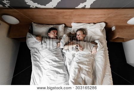 Young Couple In Hotel. Family Waking Up In The Morning On Bed. Cute Couple Waking Up After A Night S