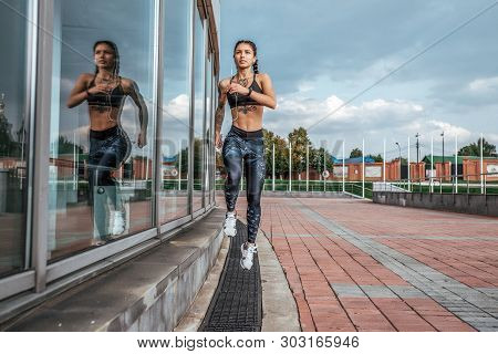 Athlete Girl Runs Jump Sports Jogging Training Summer City. Headphones Telephone. Concept Fitness Fr