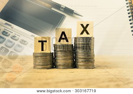 Taxation And Annual Tax Concept. A Wooden Block With Message On Stacked Coins On Wood Table Exposure