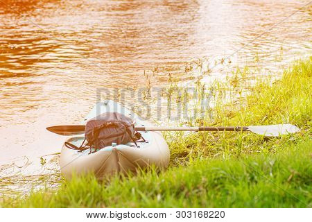 Inflatable Whitewater Kayak With A Paddle On Green Grass Shore Pack With Hermetic Bag