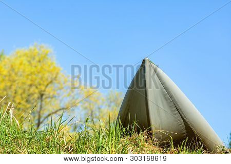 Closeup Inflatable Whitewater Kayak On Shore With Tree Branches On Blue Sky