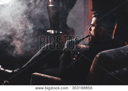 Groomed Bearded Man Is Relaxing On Lounge Near Fireplace While Smoking Hookah. He Has Tattoo On His