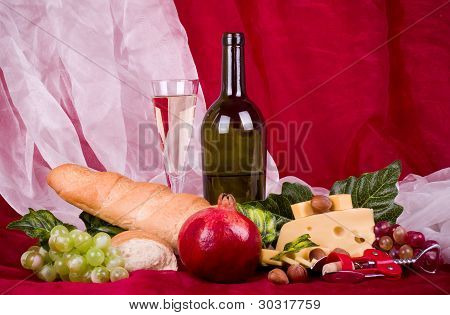 Beautiful composition with wine, grape, cheese, pomegranate and long loaf on red background poster
