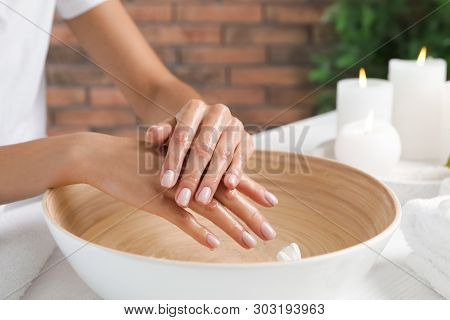Woman soaking her hands in bowl of water and flowers on table, closeup with space for text. Spa treatment poster