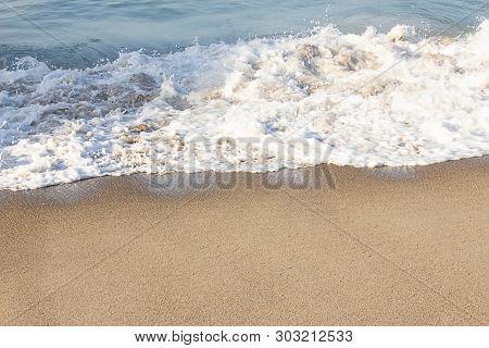Foaming Breaking Wave And Backwash Foam On A Sandy Shoreline