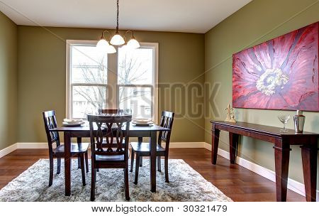 Dining Room With Green Walls And Red Painting.