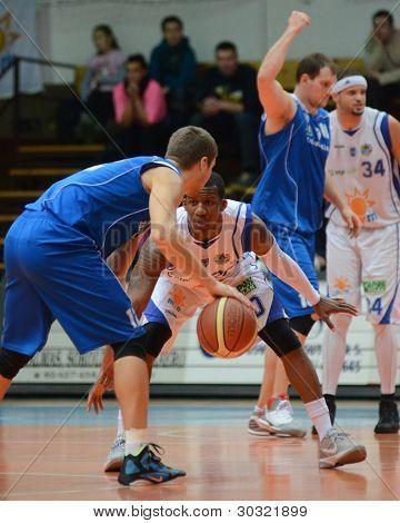 KAPOSVAR, HUNGARY – FEBRUARY 18: Kwadzo Ahelgebe (white, 20) in action at a Hungarian Championship basketball game with Kaposvar (white) vs. Fehervar (blue) on February 18, 2012 in Kaposvar, Hungary.