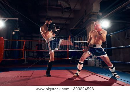 Two Angry Male Kickboxers Training Kickboxing In The Ring At The Health Club