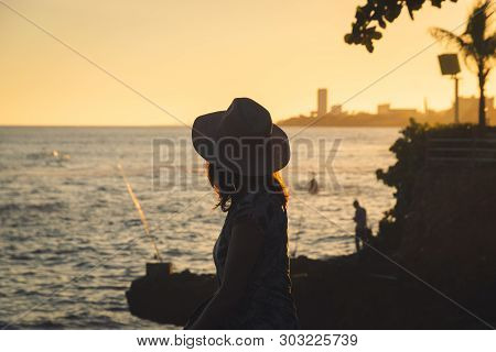 Traveler Girl Looking To The Sea In Sunset. Vacation Lifestyle. Young Girl Traveler Relaxing In Vaca