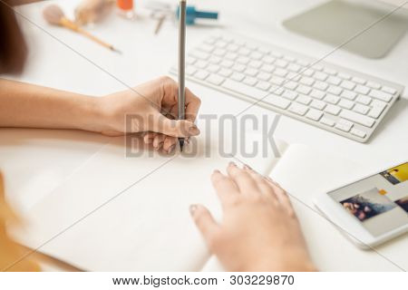 Hands of young female designer holding pencil over blank sheet of paper before drawing sketch or picture by workplace