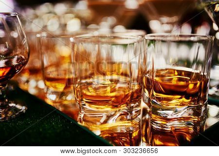 Glasses Of Whiskey On Bar Background. Lots Of Glasses Of Whiskey. Glasses Of Whiskey Or Brandy. Sele