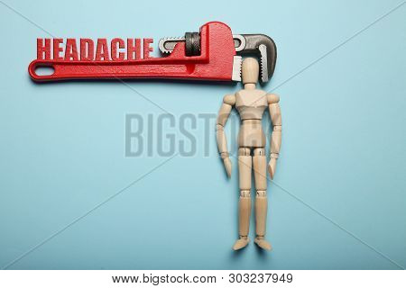 Wooden Figure Of Man With His Head Clamped In Vice With Inscription Headache. Pain, Stress, Migraine