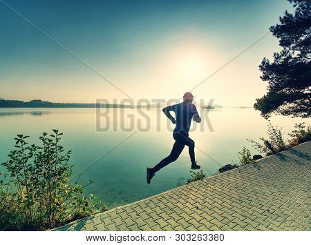 Silhouette Of Athlete Run On Sunset Background Copy Space. Man With Sportive Figure Practices Sport