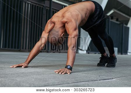 Young Muscular Sportsman Doing Stretching Before Training. Young Male Exercising With Naked Torso.