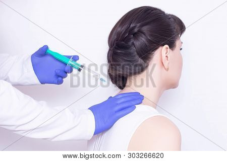 The doctor makes an injection of chondroprotector and anesthetic in the cervical vertebrae of the girl to eliminate pain and stiffness, inflammation, close-up poster