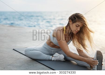 Attractive Sporty Tanned Fit Woman Wearing Sports Bra Sitting Fitness Mat Stretching, Warming-up Bef