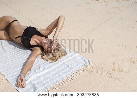 Top View Carefree Happy Female Tourist Blond Hair Wear Bikini Lie Down Sandy Beach Blanket Sunbating