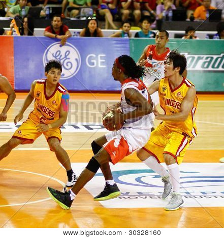 KUALA LUMPUR - FEBRUARY 19: Malaysian Dragons' Tiras Wade (white) dribbles in against the Singapore Slingers at the ASEAN Basketball League match on Feb 19, 2012 in Kuala Lumpur, Malaysia.  Dragons won 86-71.