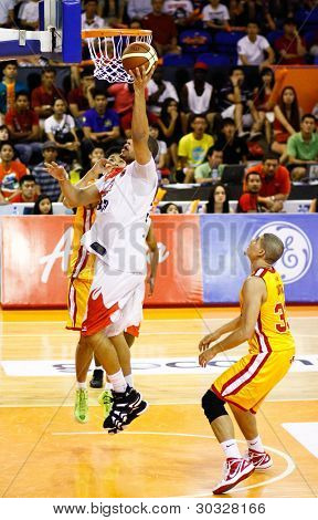 KUALA LUMPUR - FEB 19: Malaysian Dragons' B. Williams (white) goes to the hoop against the Singapore Slingers at the ASEAN Basketball League match on Feb 19, 2012 in Kuala Lumpu, Malaysia.  Dragons won 86-71.
