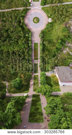 Flying Drone Above The Park. View Of The Trees And Walkways. Top View Of The Park. Photo In The Styl