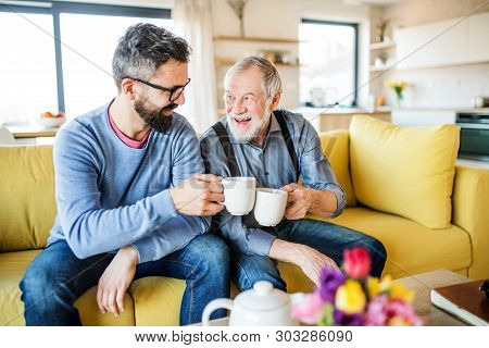An Adult Son And Senior Father Sitting On Sofa Indoors At Home, Drinking Tea.