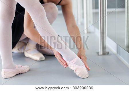 Little Ballerina And Ballet Teacher In Classical Dancing School. Female Dance Trainer Corrects Kids