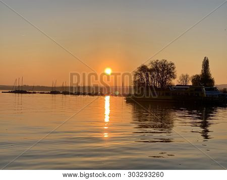 Sunset and trees silhouette over a lake
