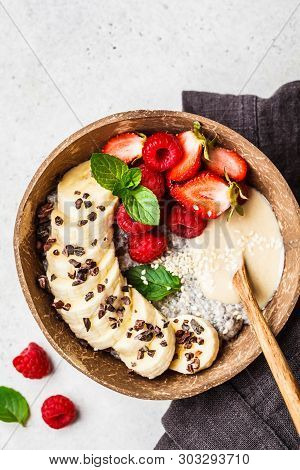 Chia Pudding With Berries, Banana, Peanut Butter And Cocoa Nibs In A Coconut Shell Bowl.