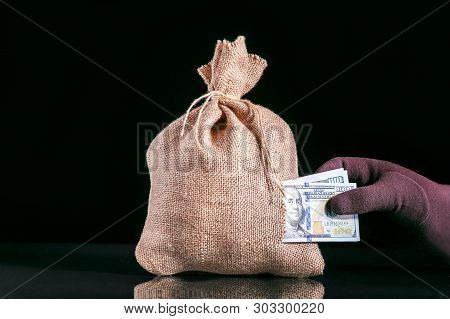 Stealing Money. Money Loss, Tear In Bag, Money Sack With Hole And Hand Grabbing A Pile Of Dollar Ban