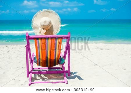 Journey. On the beach, a girl sits in a colored pareo and straw hat with her back to the camera in a beach chair, relaxation, relaxation and sunbathing. poster