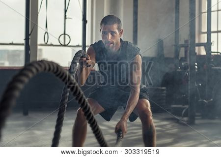 Strong young man working out with battle ropes in a fit gym. Muscular sportsman doing  excursion with ropes in workout gym. Determined guy using battle rope while doing physical training.