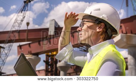 female foreman inspects object at building site. Construction of central ring car road. poster