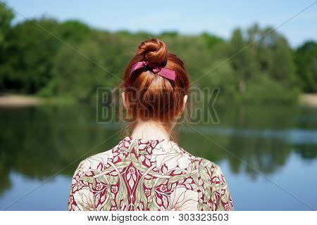 Back View Of Unrecognizable Young Woman With Floral Dress And Red Hair Bun Looking At Lake In Solitu