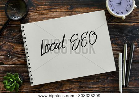 Top View Of Magnifying Glass,clock,pen,plant And Notebook Written With Local Seo (search Engine Opti