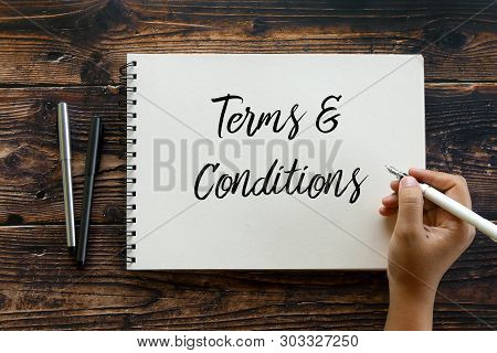 Top View Of Pen And Hand Holding Pen Writing Terms And Conditions On Notebook On Wooden Background.